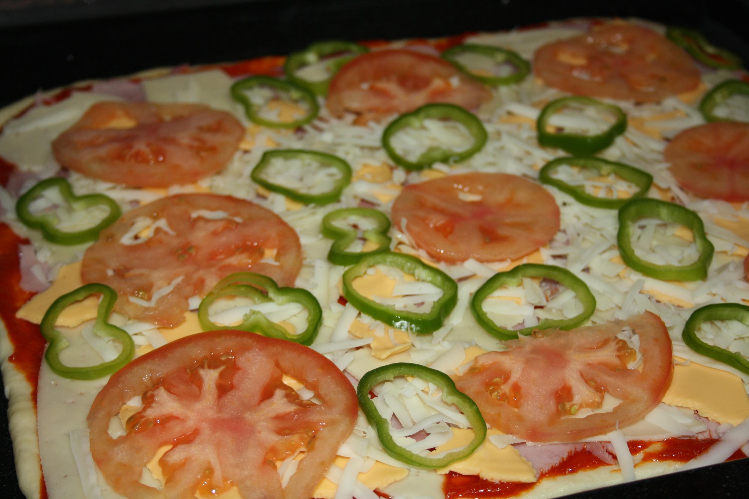Las rodajas de tomate sin piel, rallamos el queso y el pimiento en dodajas finas.