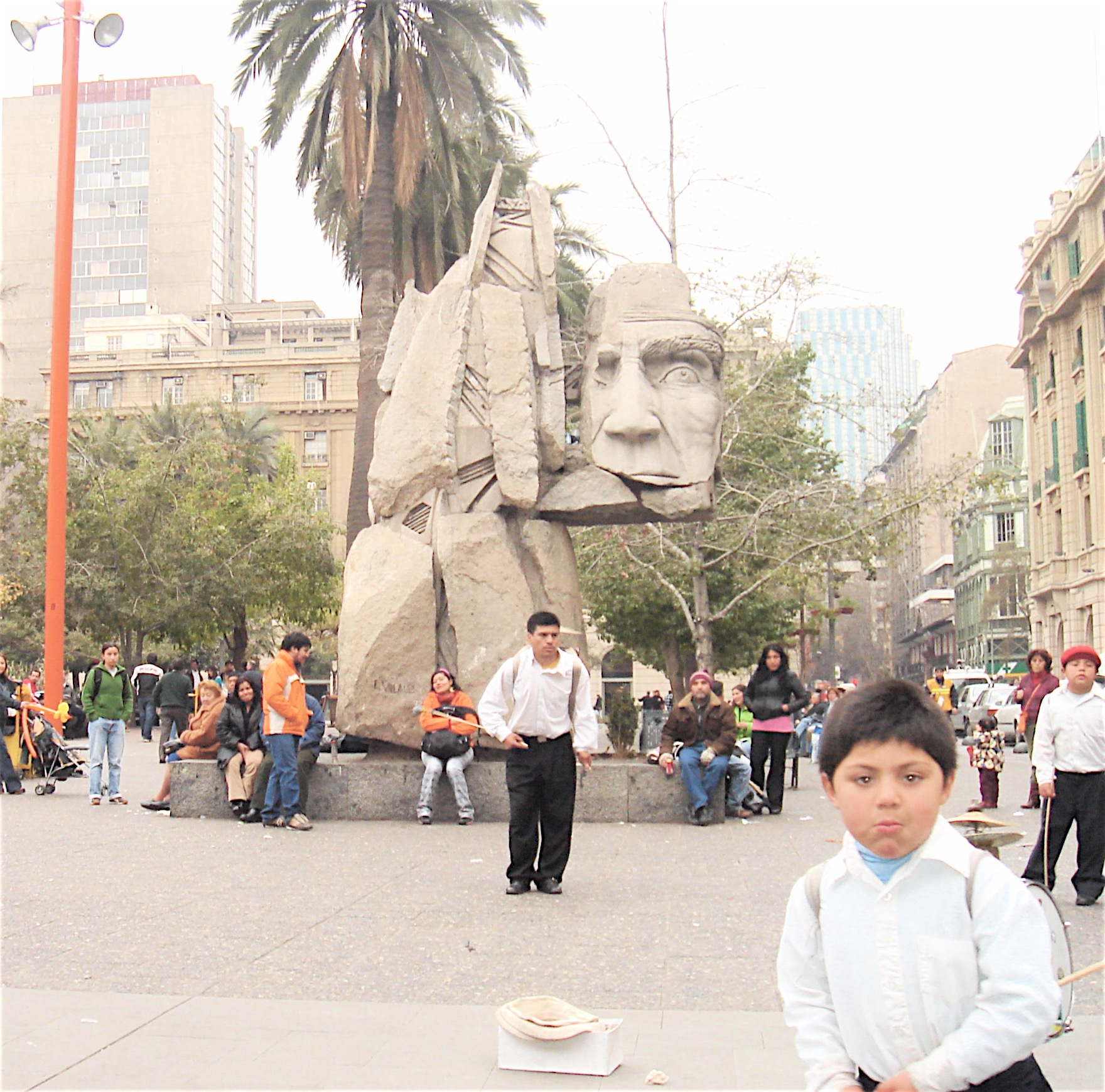 Near the center of Santiago. Palm trees, monuments, and street performers