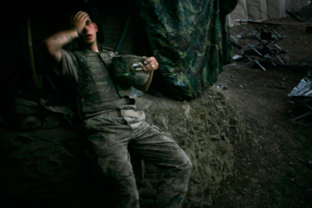 AFGHANISTAN. Korengal Valley. 2007. A soldier from 2nd platoon rests at the end of a day of heavy fighting at the 'Restrepo' outpost. The position was named after the medic Juan Restrepo from 2nd Platoon who was killed by insurgents in July 2007.