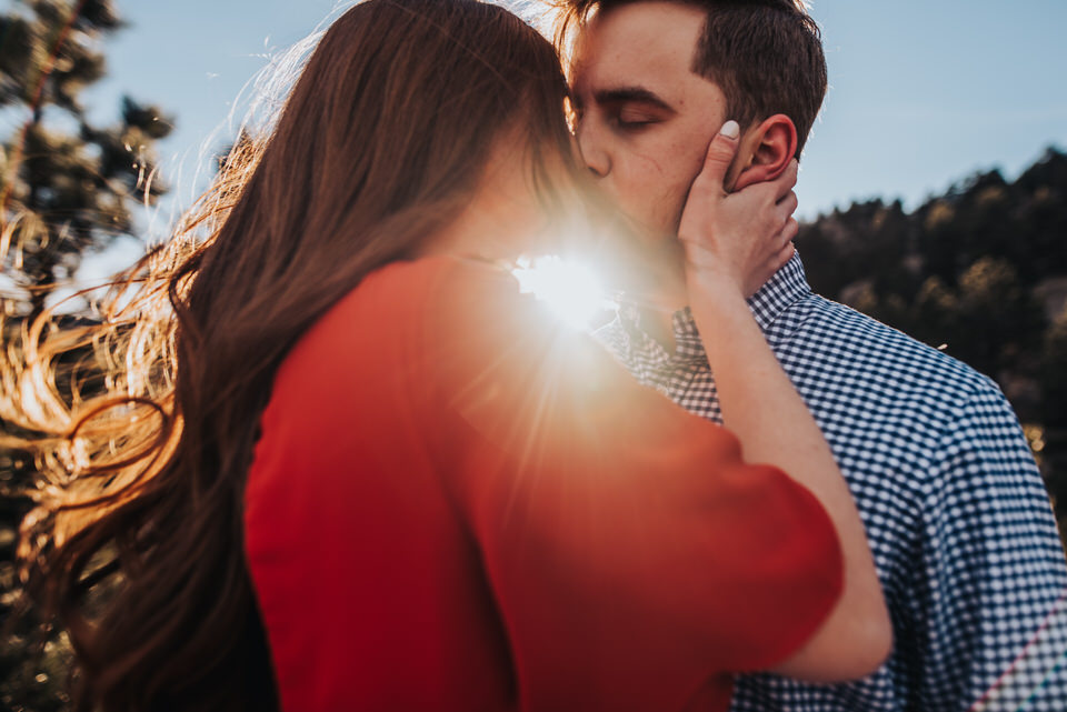 Couple kissing on mountain top with a sun-flare between them.