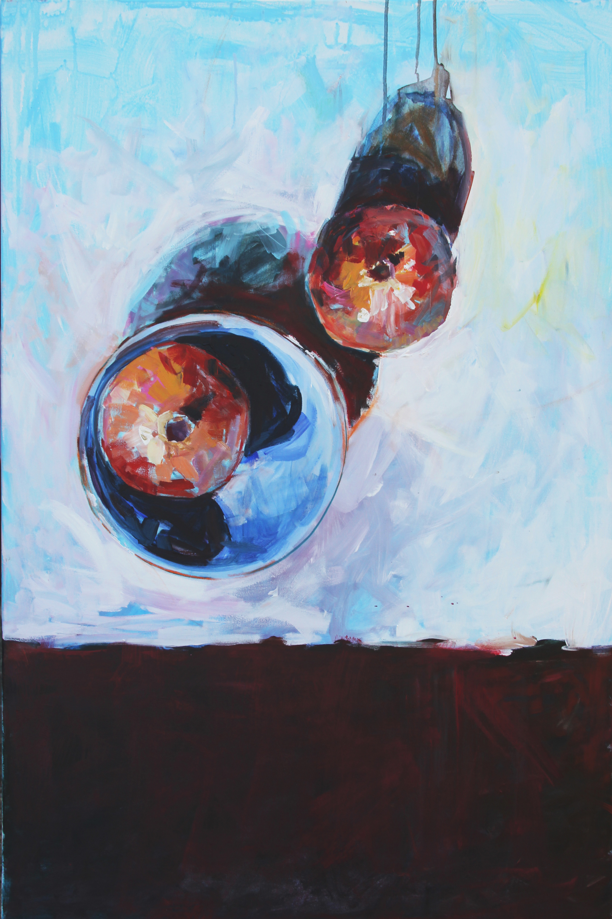 Two Pomegranates on a table, one in a blue bowl