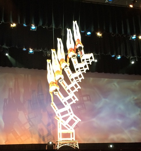 The woman on the bottom climbed on first. Her friend then climbed up with her chair Repeat until there are 5 woman standing on their heads on a stack of chairs.