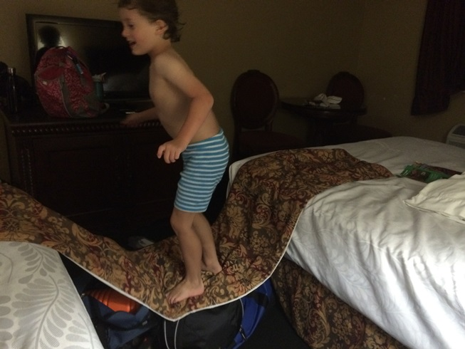 Tag making a bridge between the two beds using luggage. I guess it's better than him walking on the floor.