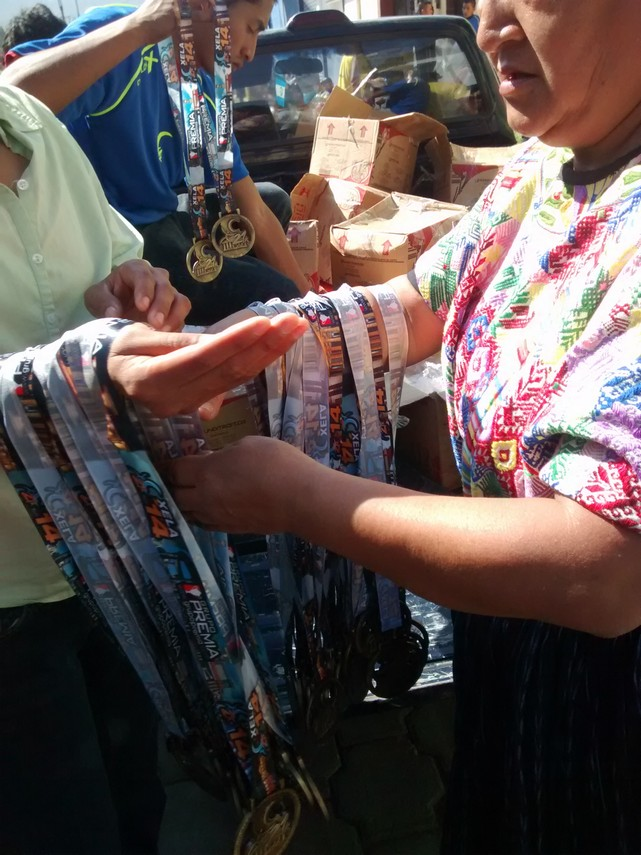 Race medals being prepped for distribution to runners.  Note the woman's traditional Mayan traje.  Also very common throughout the country.