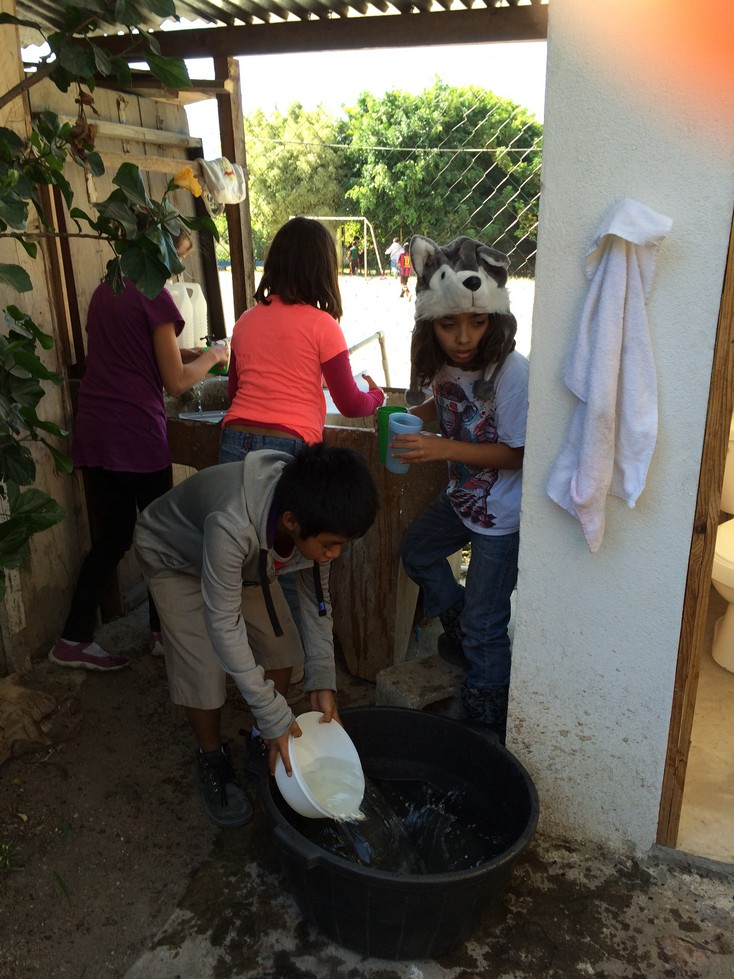 Three 4th graders (my students) and one 5th grader filling the BIG water bucket.