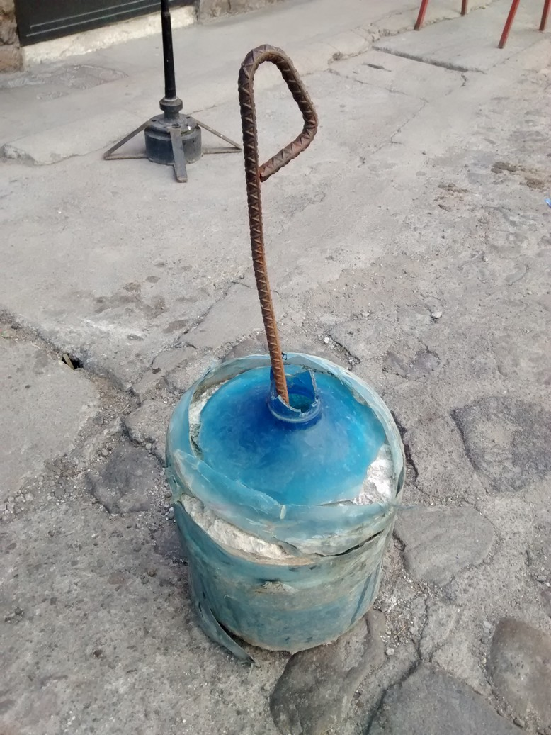 Build your own traffic cone (with a handle) by pouring cement in an empty jug of water and topping it with a bent piece of rebar.