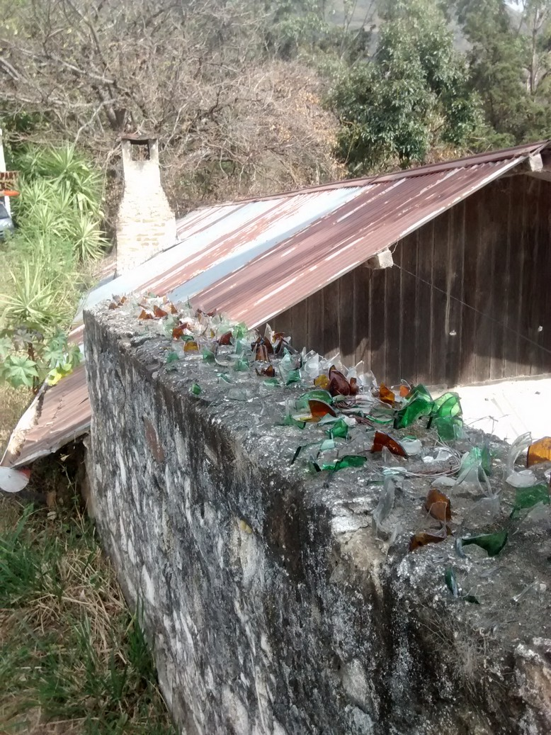 Recycle your glass bottles by cementing them into your rock fence. It's the environmentally friendly solution to home security.