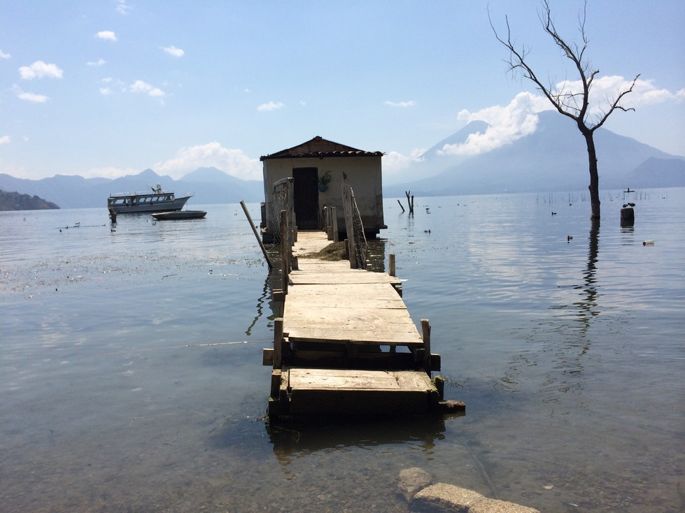 A house and walkway siton the rising lake.