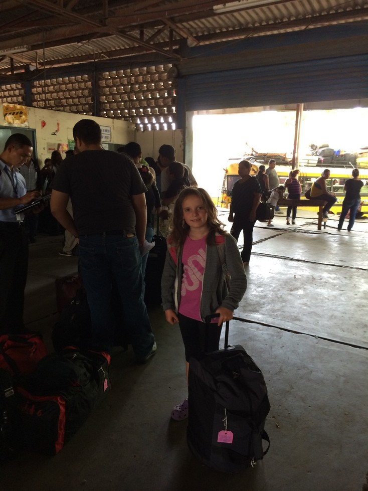 Customs in Nicaragua - Ela is in charge of her backpack and the bag on wheels. I was responsible for the 2 large bags, my backpack, the food bag and the pillow. Look at the  bus we didn't take (background). I'm not sure our bags would fit anyway.