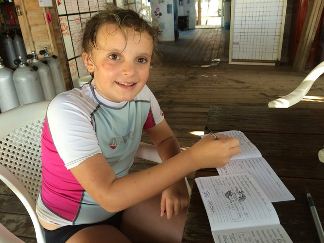 Ela completing her scuba diver book, recording the day's dive site, water temperatures and depth of dive. On this day, she also noted seeing an adult  Hawksbill Sea Turtle .