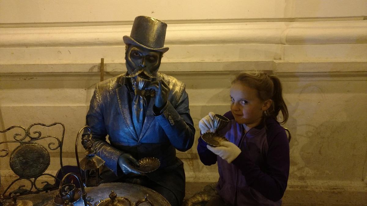 Ela having tea with a street performer.