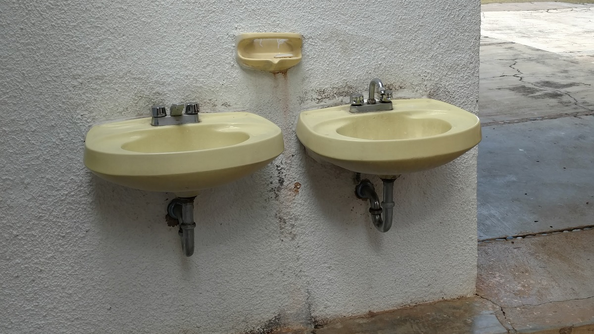 Sinks literally outside of the bathroom. Note the small bar soap but no hand towels.