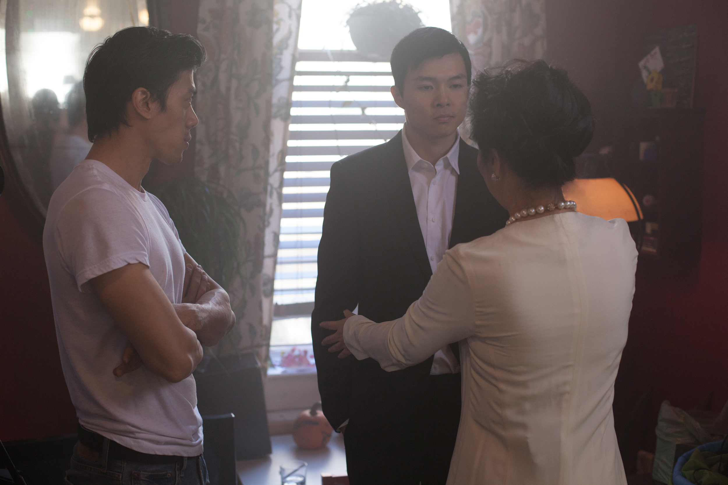 Director Leon Le rehearsing a scene with actors Zilong Zee and Wendy Huang before a take.