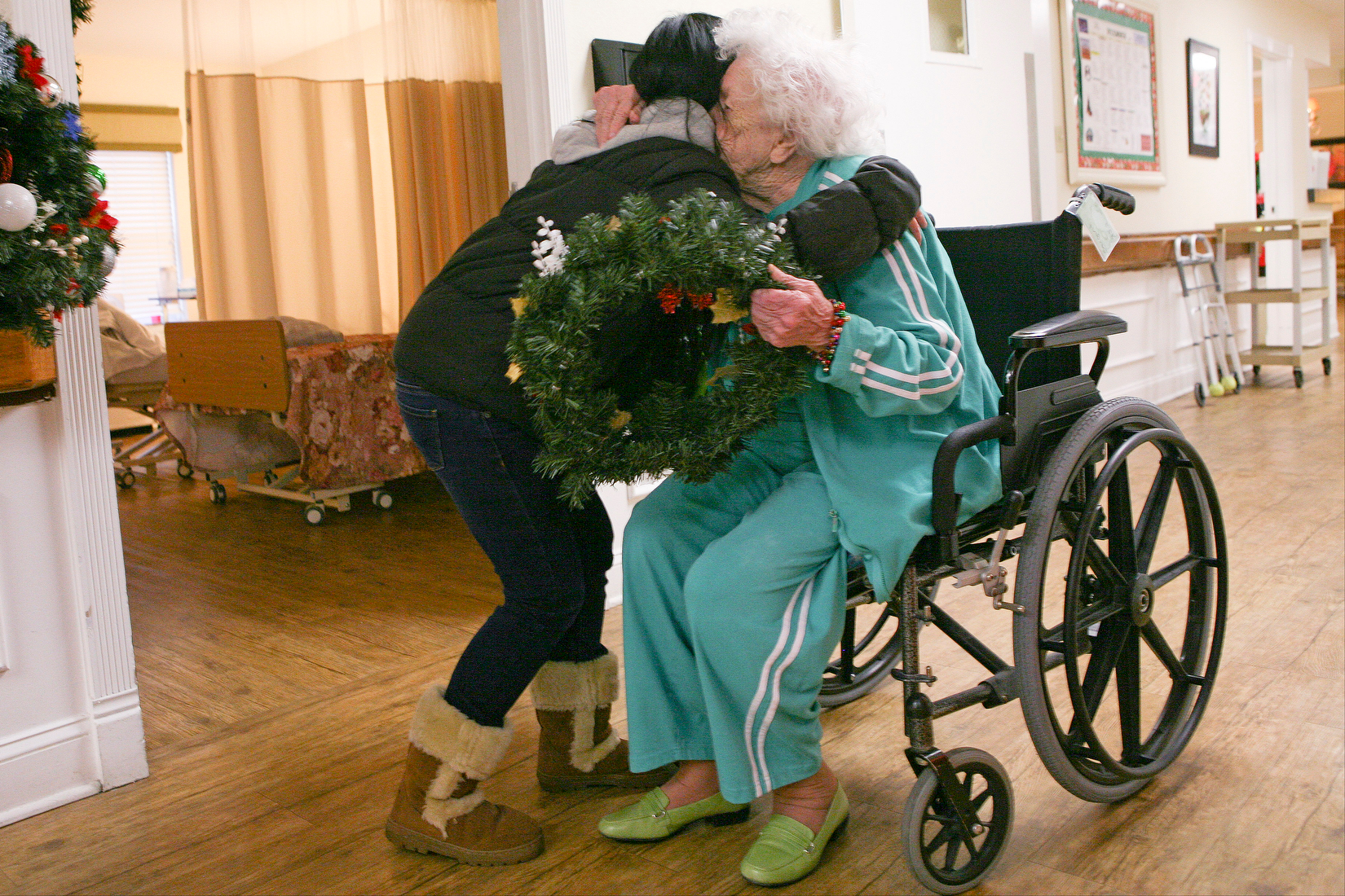 "Kim Nguyen (left) hugs Eva Sergeant, 95, after giving her a wreath at Community Outreach's Young at Heart distribution of wreaths at Mayfair Manor in Lexington, Ky. Sergeant reached for Nguyen after being handed a wreath, saying that it was ""so nice"" to have a visitor. Afterwards Nguyen said the hugs and smiles she received from residents were well worth the time spent making the wreaths and handing them out."