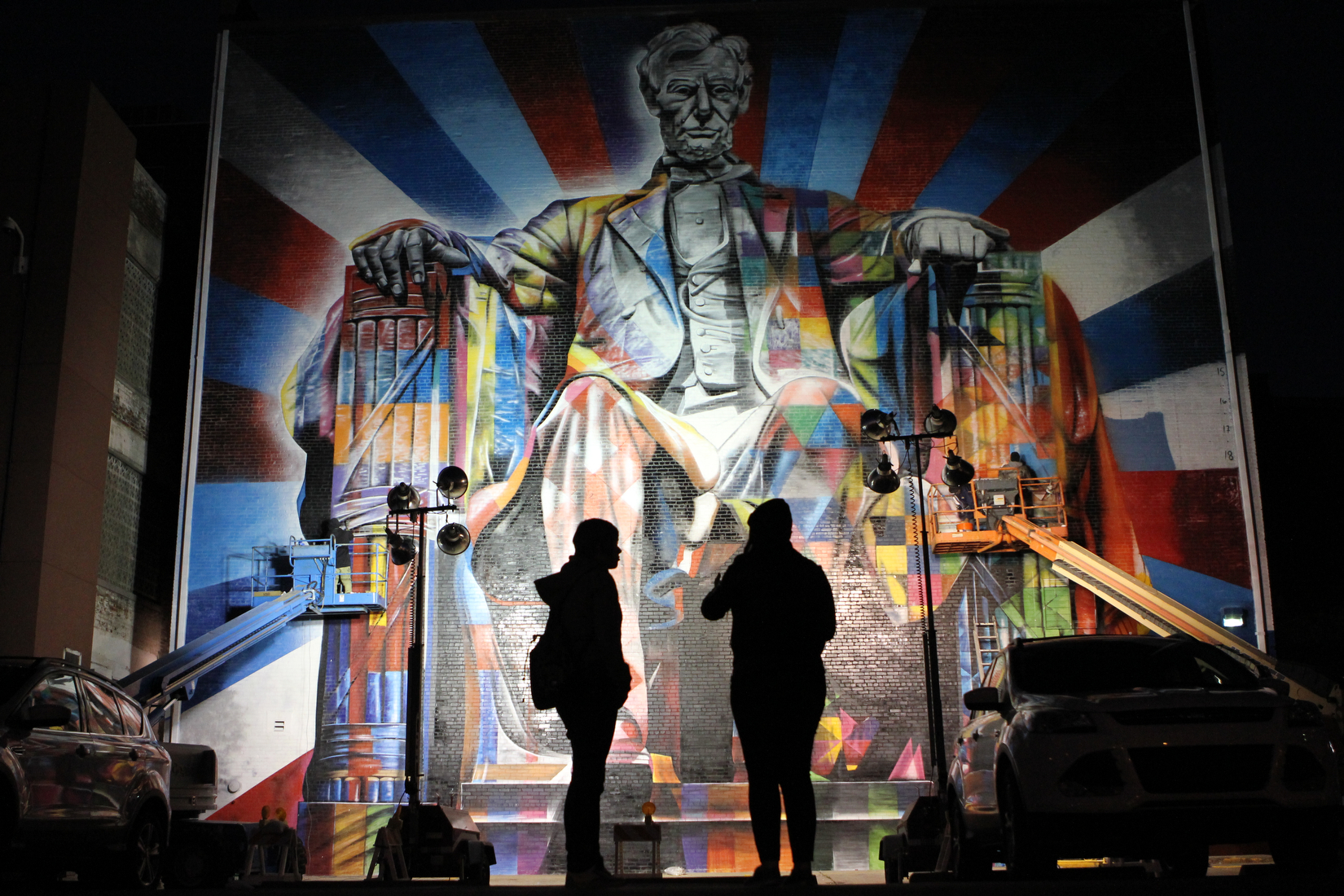 Late into the night Mandee Robinson (right) and Elizabeth O'dell watched Brazilian street-artist Eduardo Kobra and crew put the finishing touches on a mural of Abraham Lincoln on the rear of the Kentucky Theater in Lexington Ky.