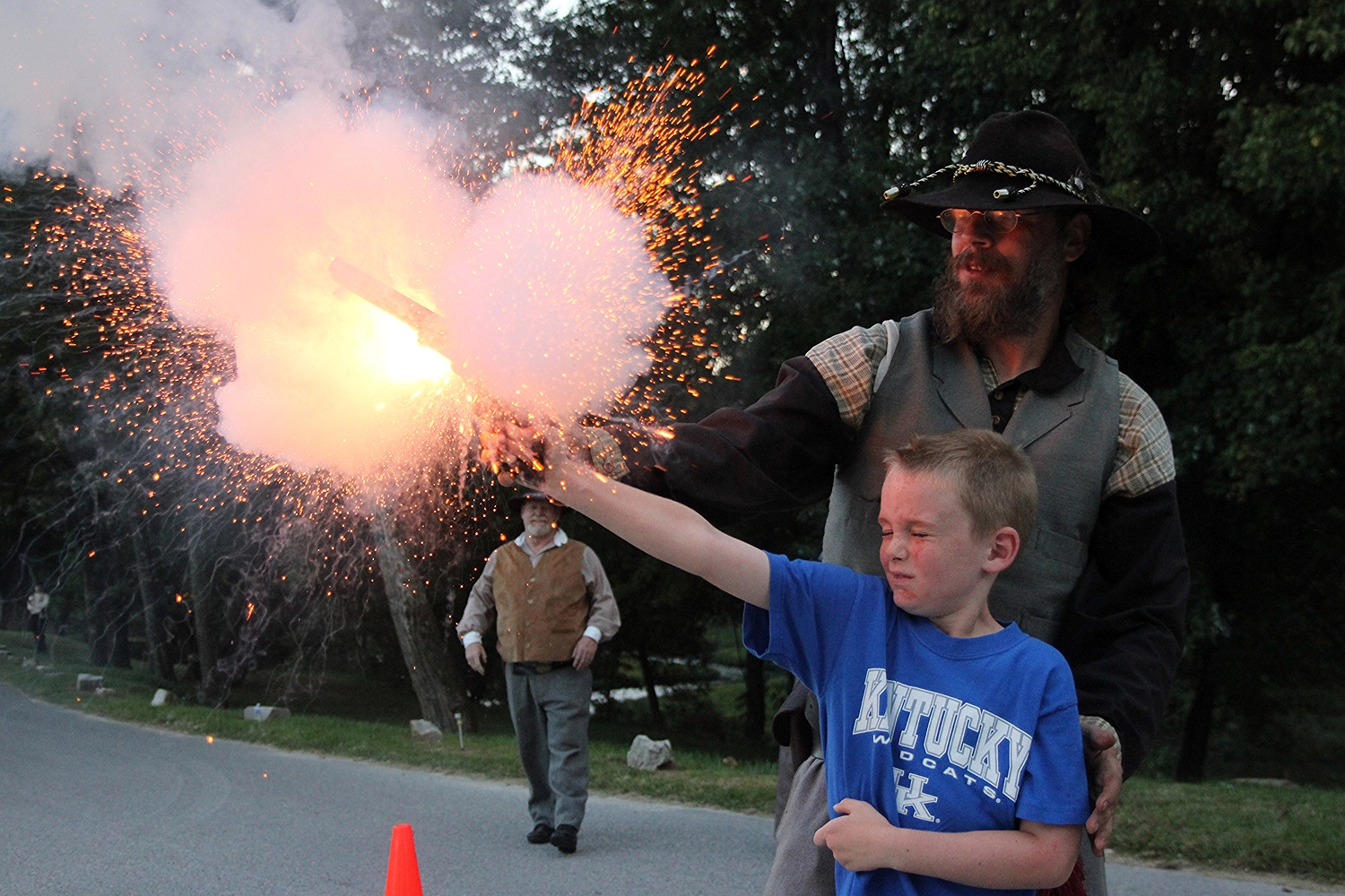 "Hayden Willett, 7, of Elizabethtown, flinches during his trip through 'White Mills Then and Now' as the gunpowder in a .44-caliber Colt 1851 Navy Revolver explodes. Known as a ""chain fire,"" the explosion was a fairly common occurrence during the Civil War, when revolver technology was in its infancy. If lead bullets were loaded instead of cream of wheat, Hayden and Munfordville Civil War re-enactor Robert Smith could have been seriously maimed."