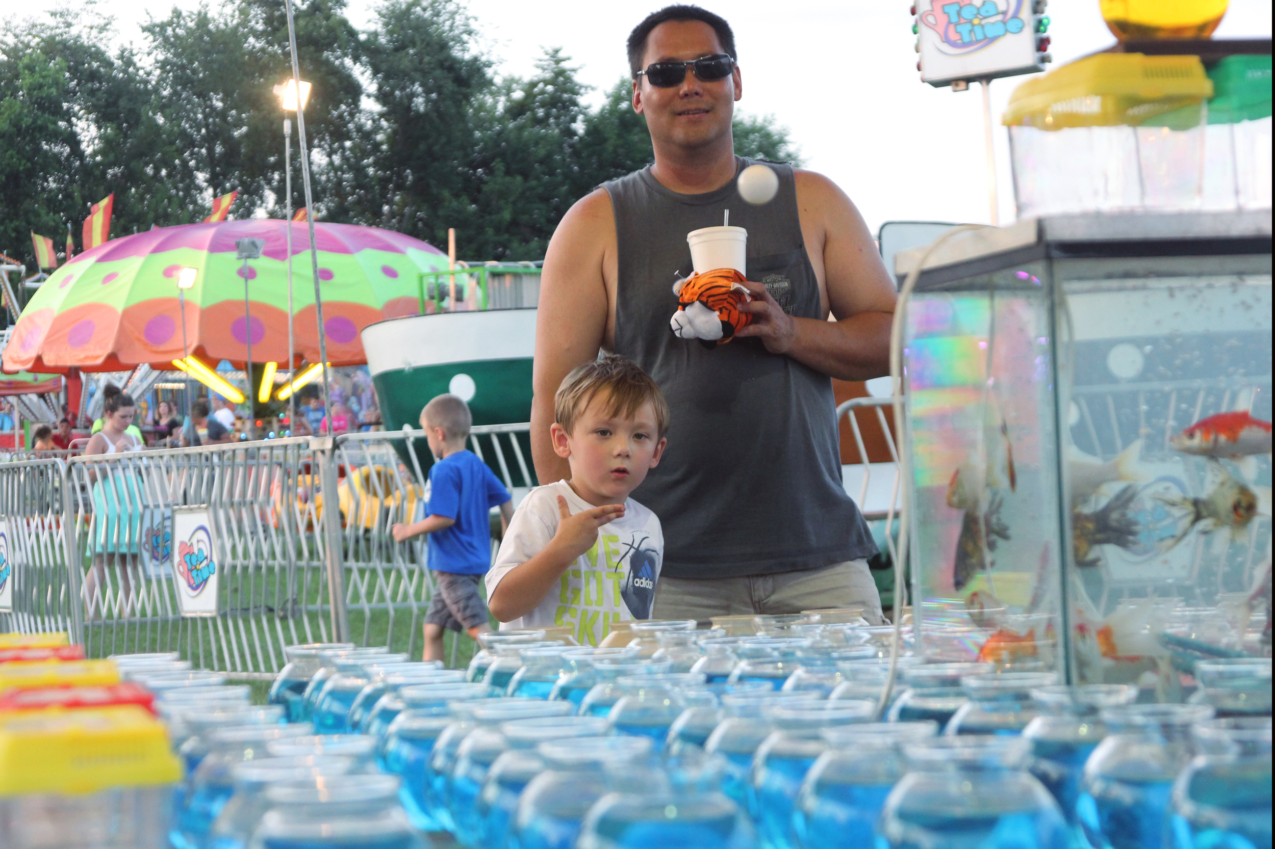 Ryan Watters, 4, throws his 12th ping-pong ball at the Pulaski Fair's goldfish toss. He missed.