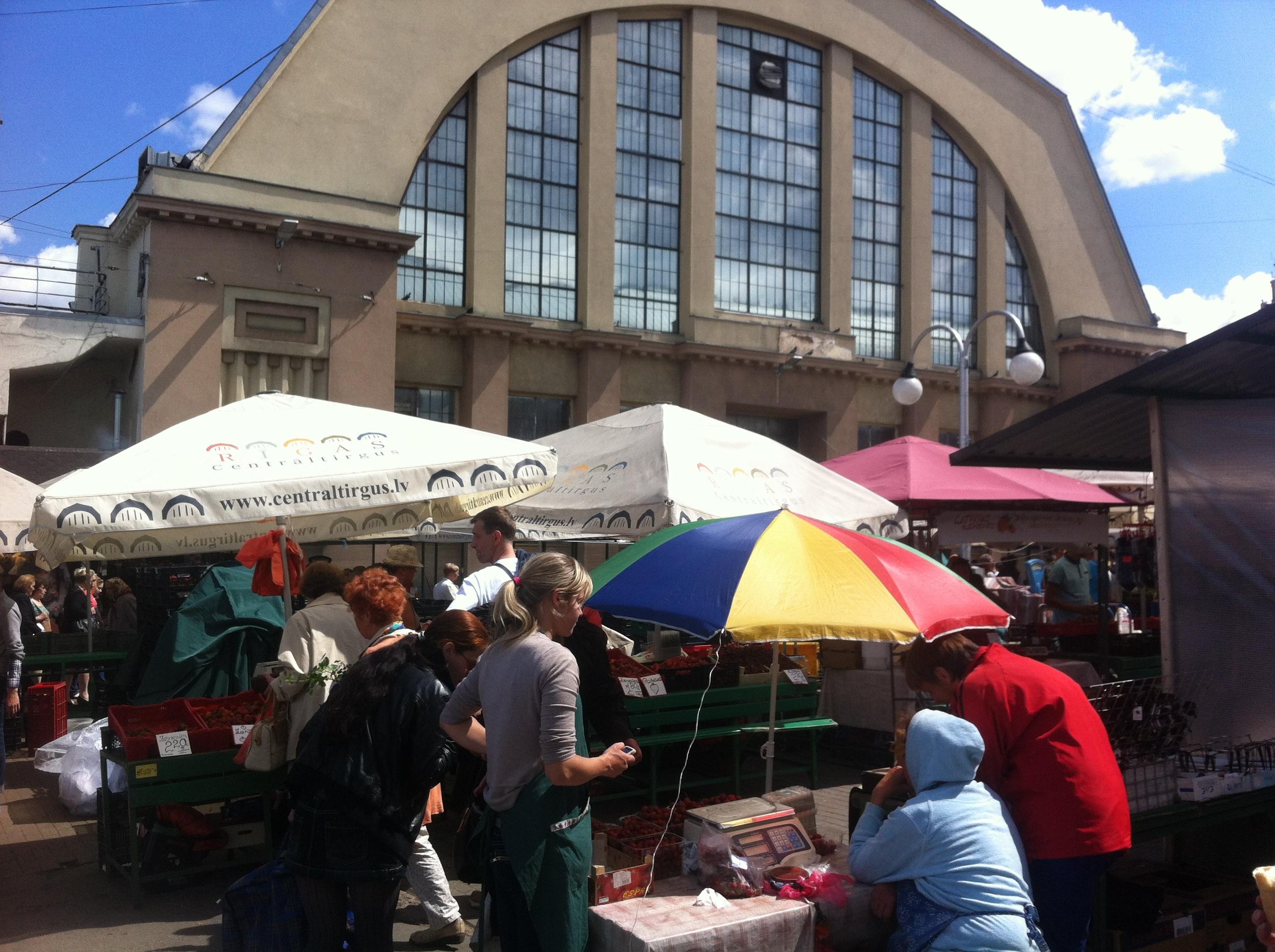 Outdoor market stands surrounding Riga Central Market's Art Deco inspired indoor market