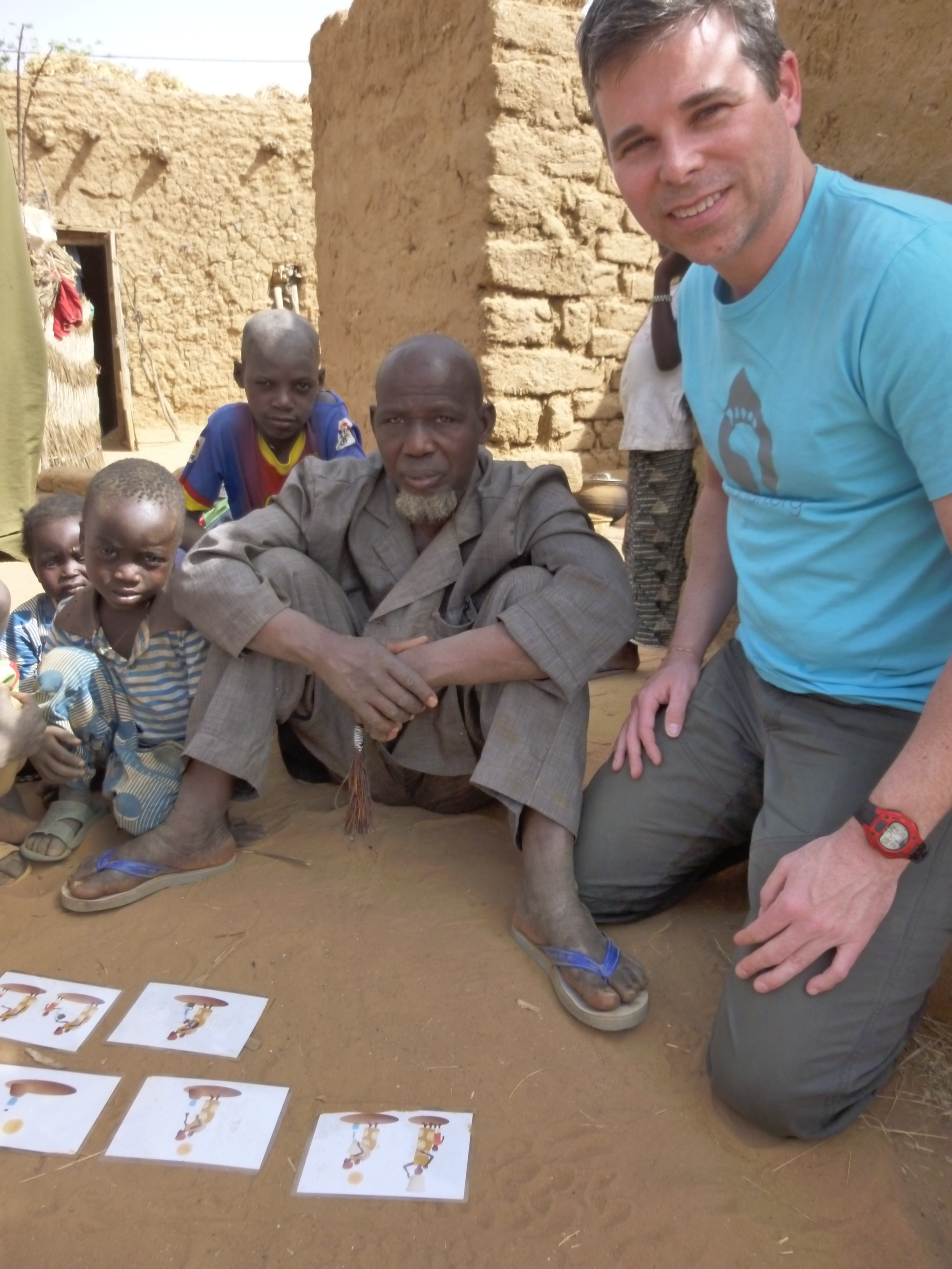 Testing the design of newly created water education materials with a man and his sons in the village of Latta.
