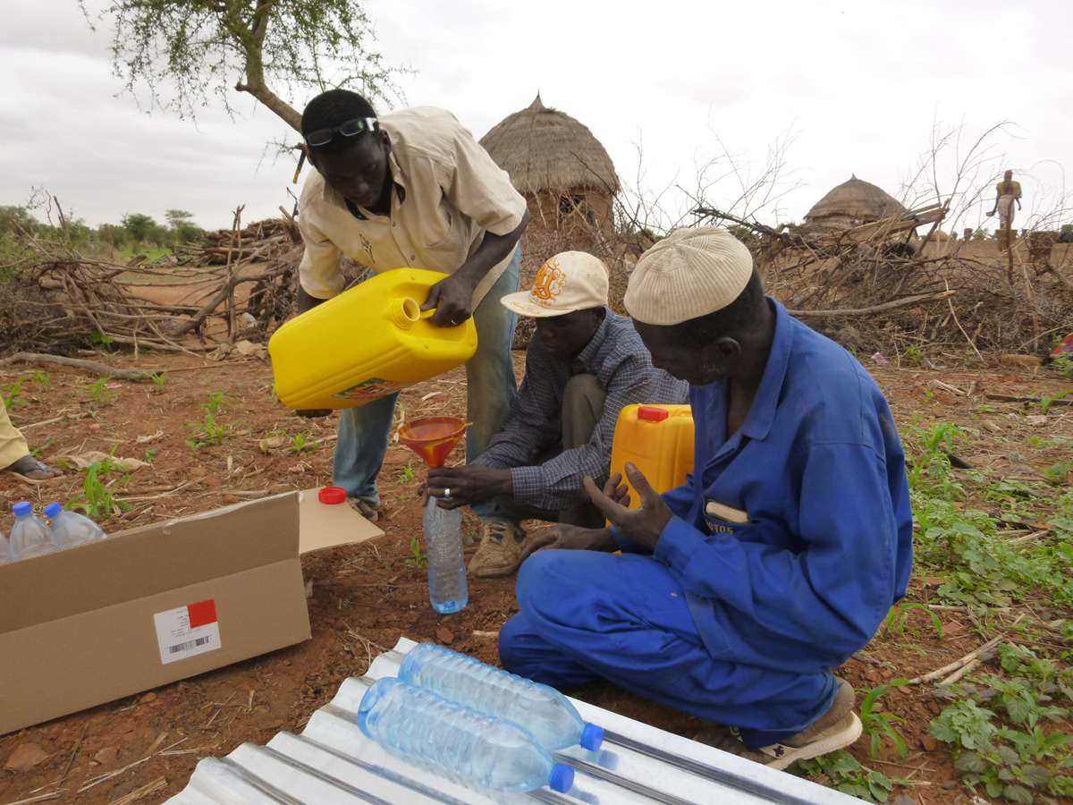 Beginning the Wayna Hina Project: Mounkayla, Alhasan, and Nuhu set up their new solar disinfection system in the Toure bush.