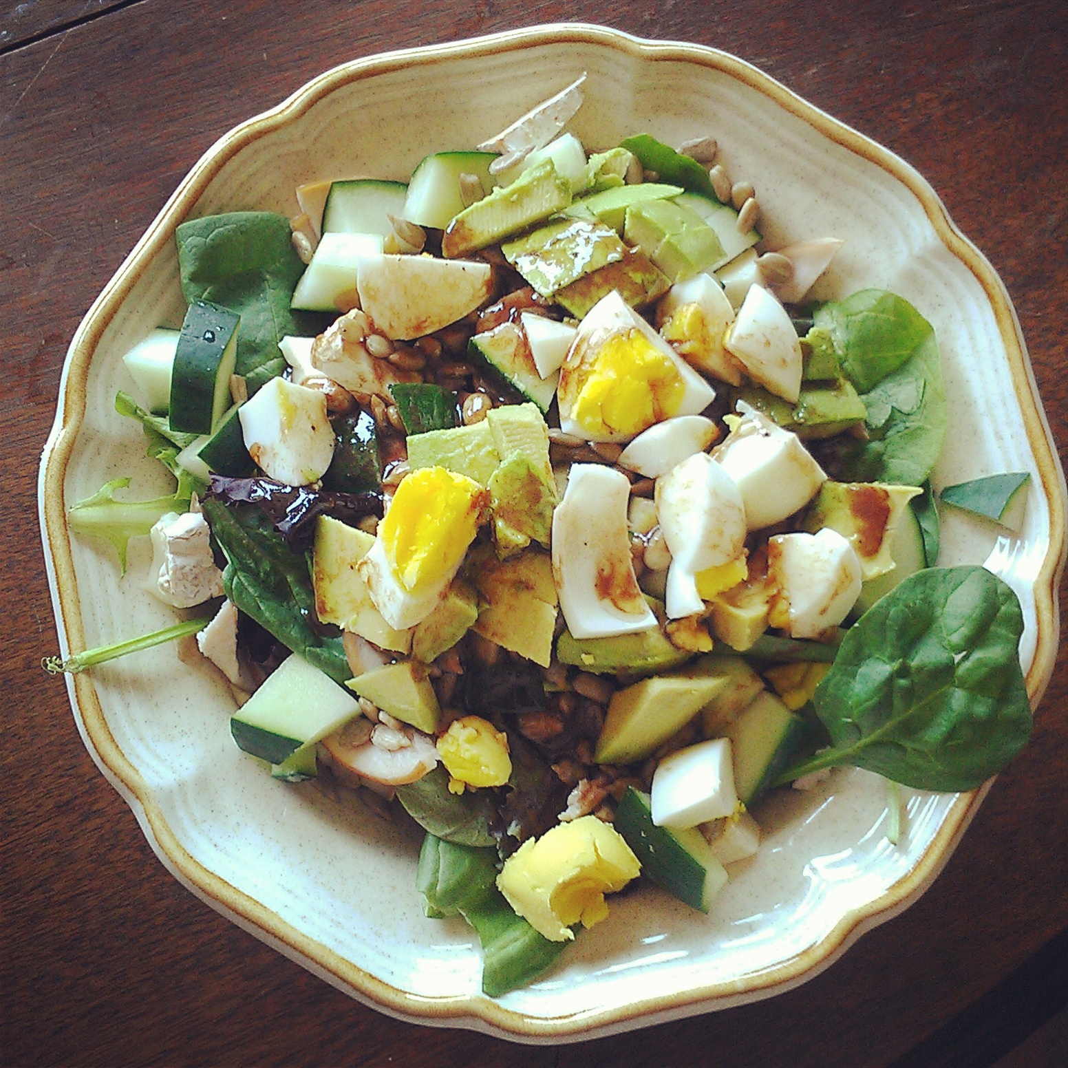 salad with cucumber, avocado, olives and soft-boiled eggs