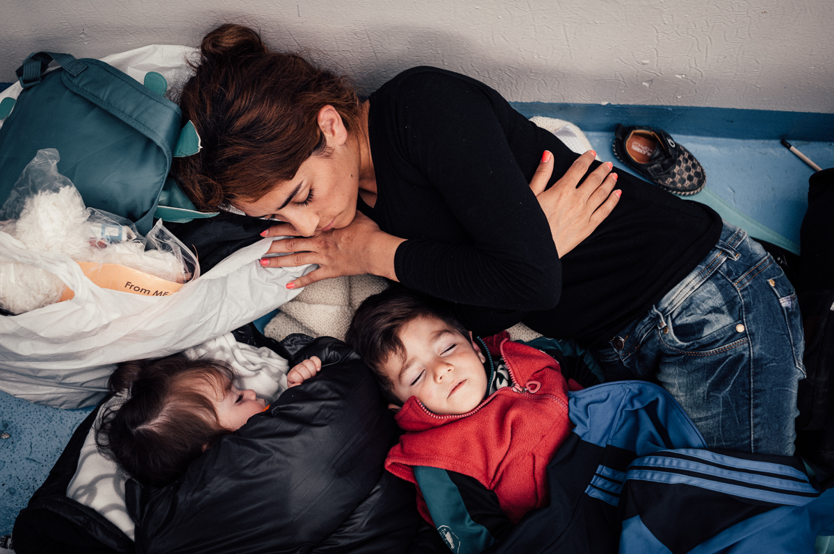 A mother and her two young children fall alseep on the ferry taking her from the Greek island of Lesvos to the Greek mainland. They are headed for Germany in hope for a new life away from the Syrian war. Oct 7, 2015.