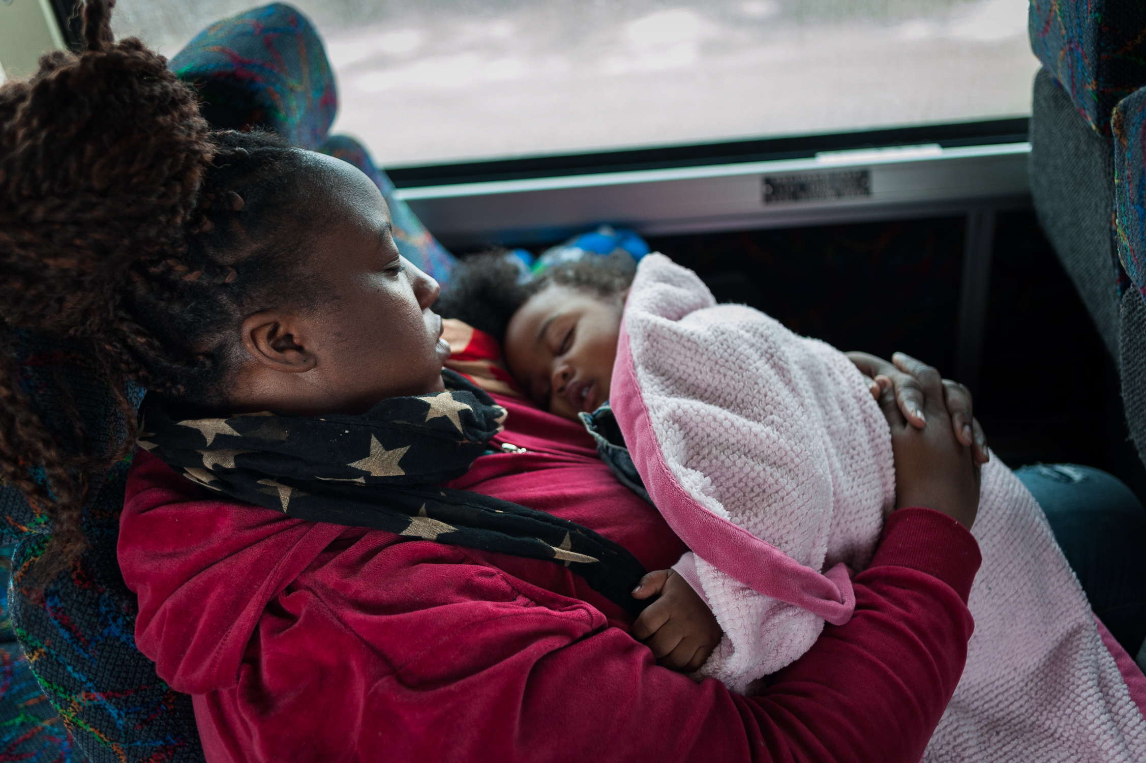"""Candis, 31, and her daughter Camryn, 1, on the way home from visiting John, Camryn's father, at the Wyoming Correctional facility on this day trip. Camryn was conceived during a so called """"trailer"""" visit, one of the weekend visits that exist at many maximum security prisons. March 15, 2014."""