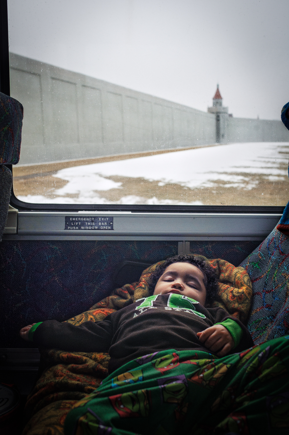 Jeremiah, 2, asleep as the bus is passing Attica prison in the early morning hours. Jeremiah is on his way to see his mother at Albion Correctional Facility. Albion is the largest women's prison in NY state, 20 miles from the Canadian Border. Jeremiah lives in the Bronx with his grandmother. March 8, 2014.