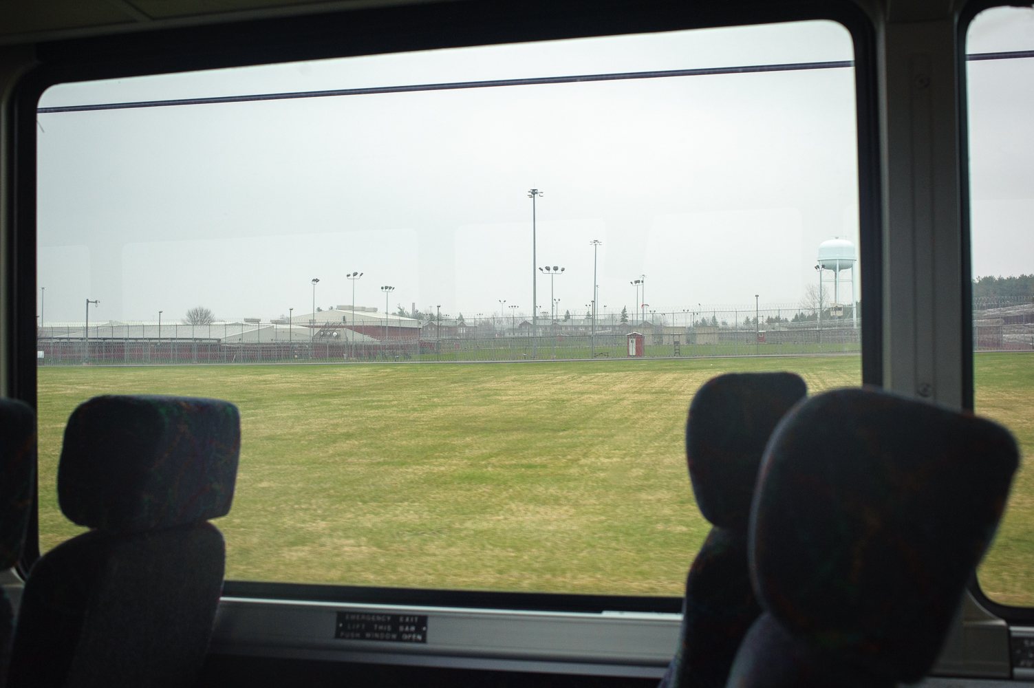 The view of Orleans Correctional Facility from the bus. Like many New York State prisons, it is hundreds of miles from New York City, where many of its prisoners come from.  Every Friday and Saturday night hundreds of New Yorkers, mostly women, many with children, undertake 24-hour trips and get on private buses and mini vans to drive all night in order to spend a few hours the next day with their husbands, brothers, mothers and fathers, who have been placed in prisons hundreds of miles from the city. April 26, 2014.