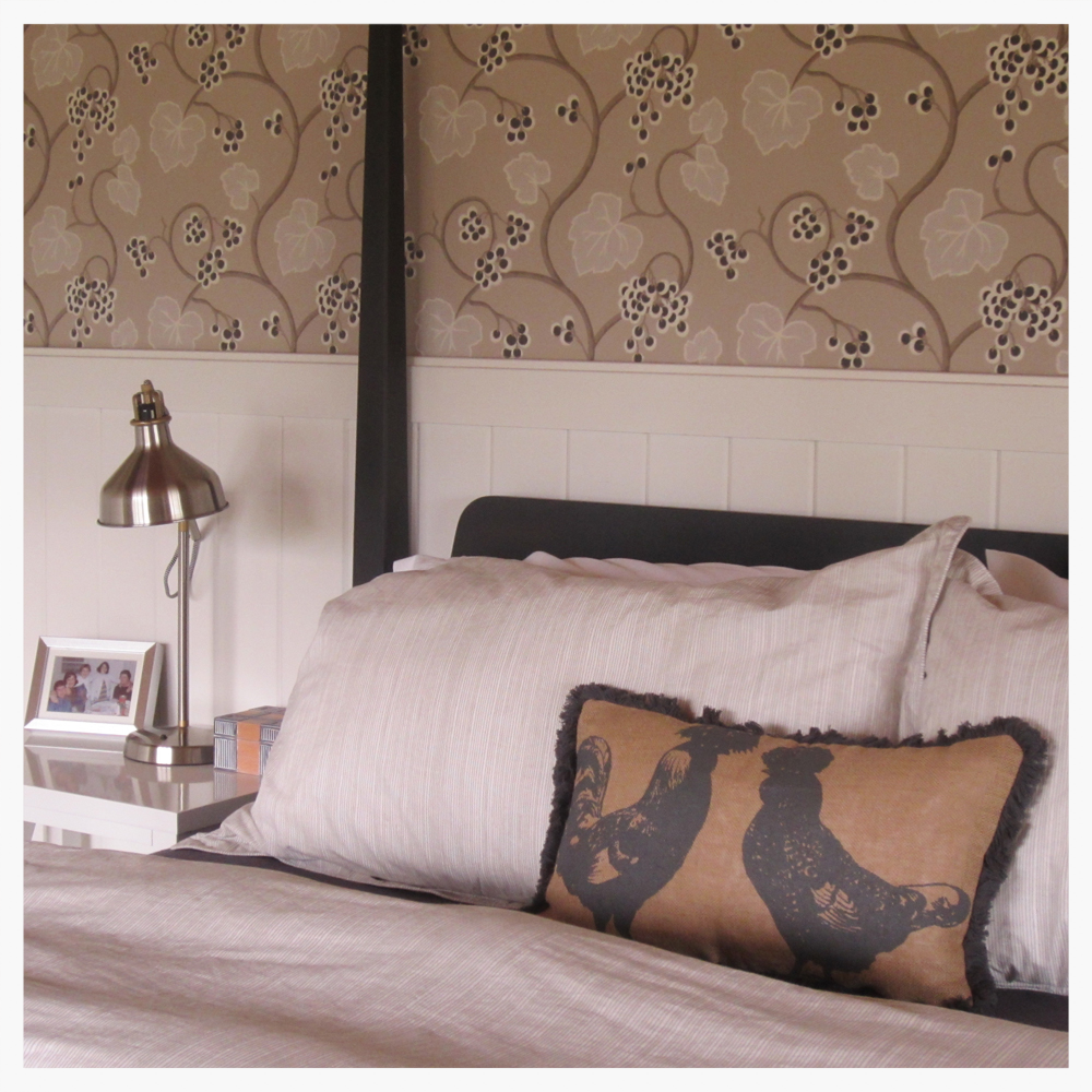 Wine Country retreat master bedroom gets comfy four-post bed in charcoal gray. Walls are covered in neutral-color grapevine motif wallpaper imported from Britain. Extra-tall white wainscoting is a country-modern touch.