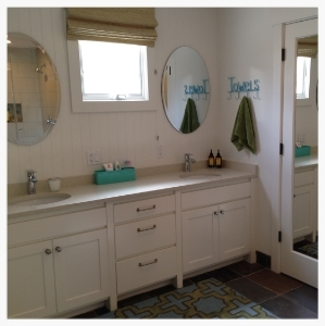 Guest bathroom gets a modest renovation with non-custom-made cabinets. Inexpensive mirrors are from a local hardware store. Slate floors are skid-proof for wet feet coming in from the outside pool area.