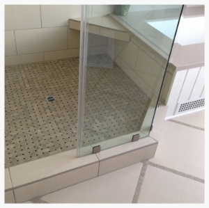 Shower detail showing classic basket weave tile motif in limestone mosaic, combined with less expensive ceramic tiles in large brick-shaped and square sizes. Taupe-color grout blends the materials seamlessly, and doesn't stain.