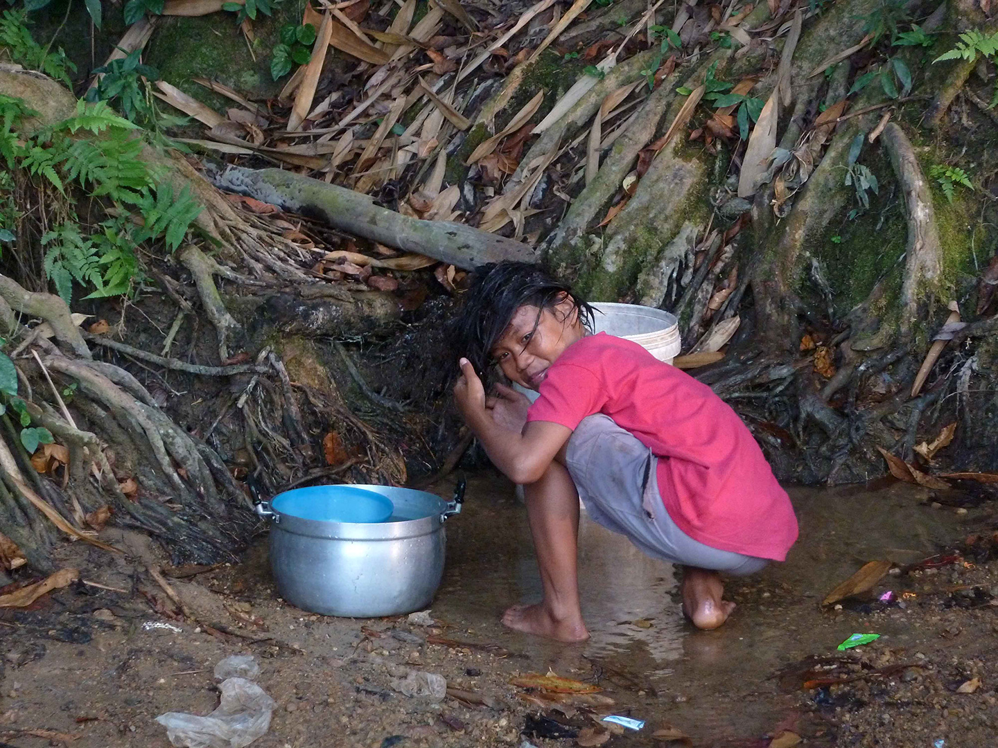 A child collecting water and washing her hair (Fung Na community)