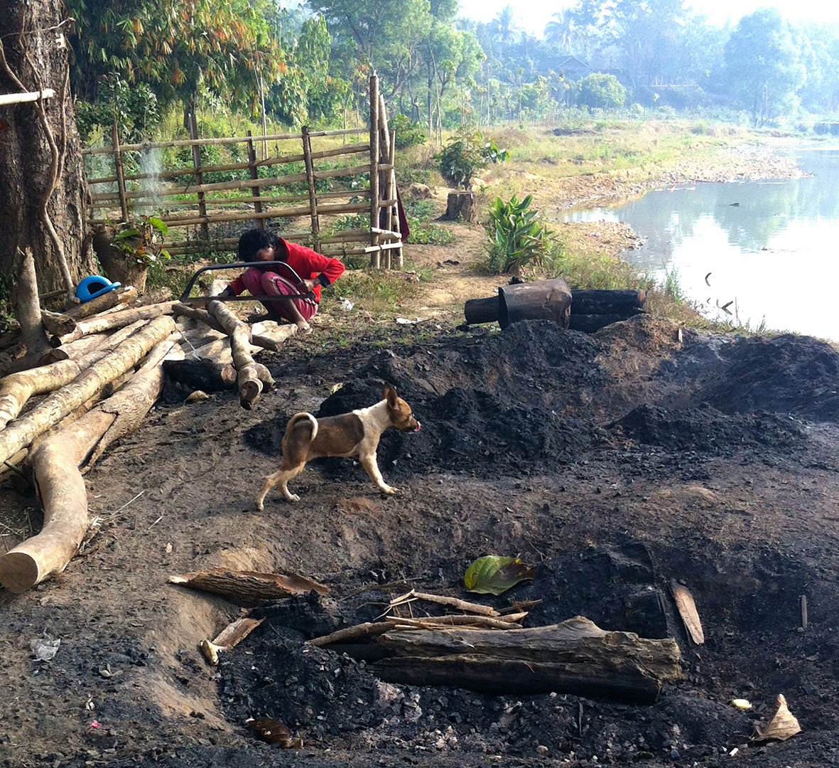 A girl taking a day off from school to help her family make charcoals (Ban Mai community)