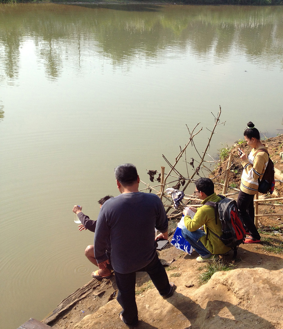 Collecting a sample from the water source (Ban Mai community)