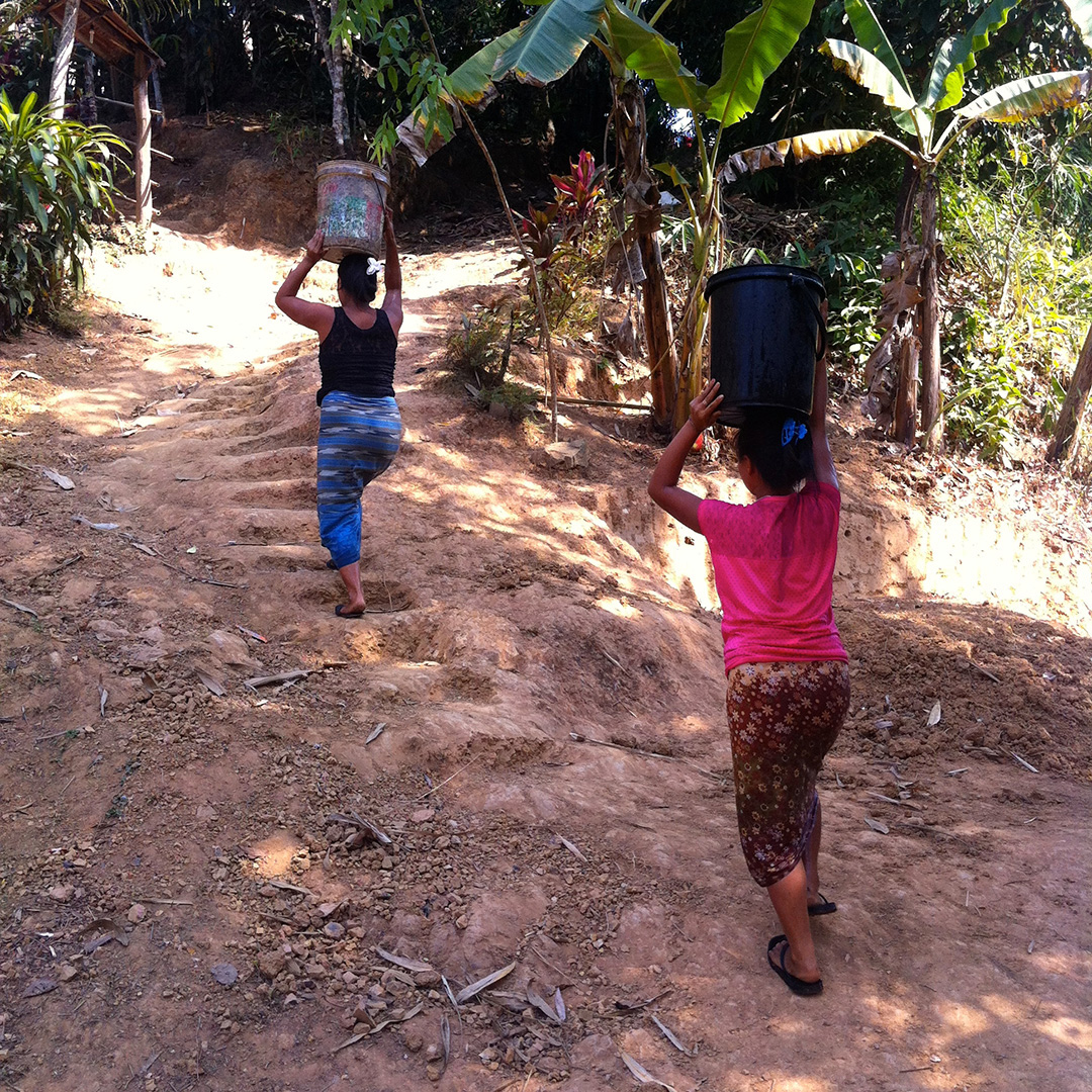 Women carrying water back to their houses (Song Ka Lia community)