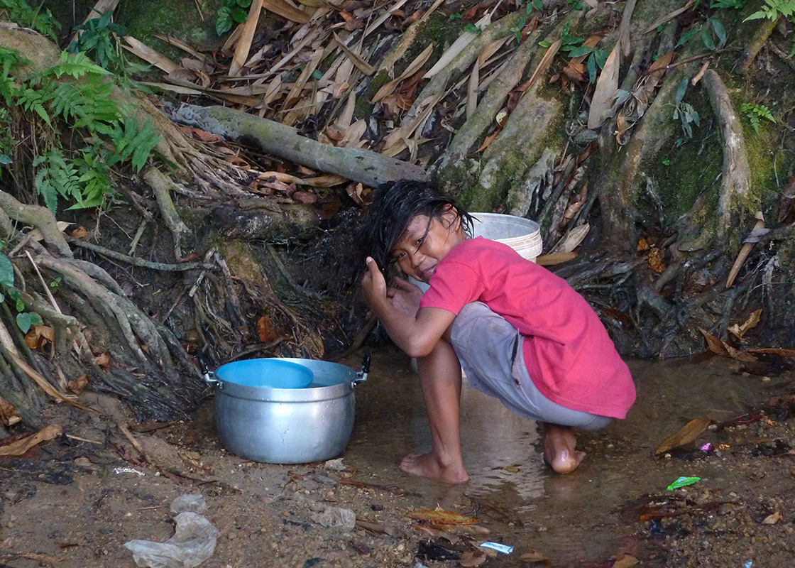 A girl collecting water and washing her hair