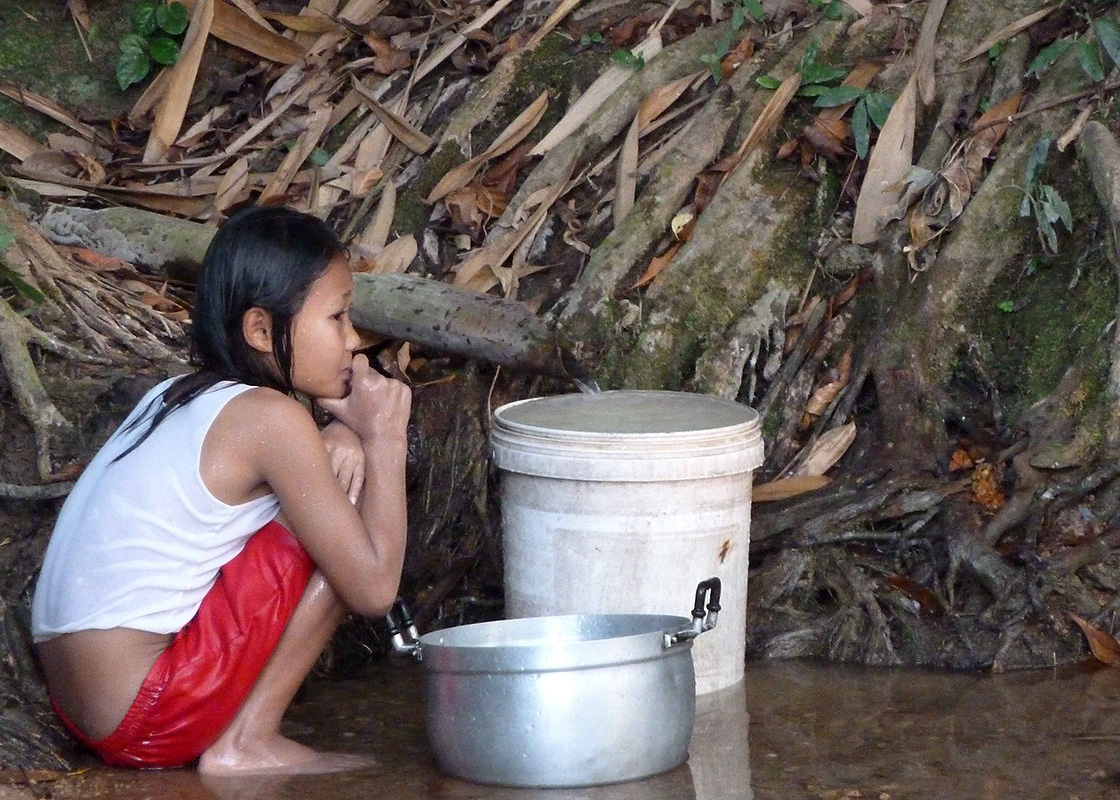 A girl collecting water from the spring