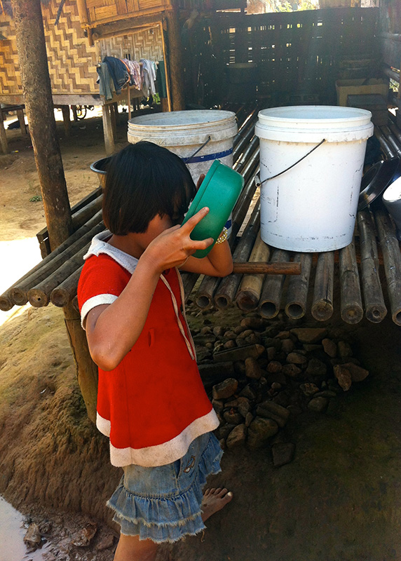 A girl drinking water collected from the river