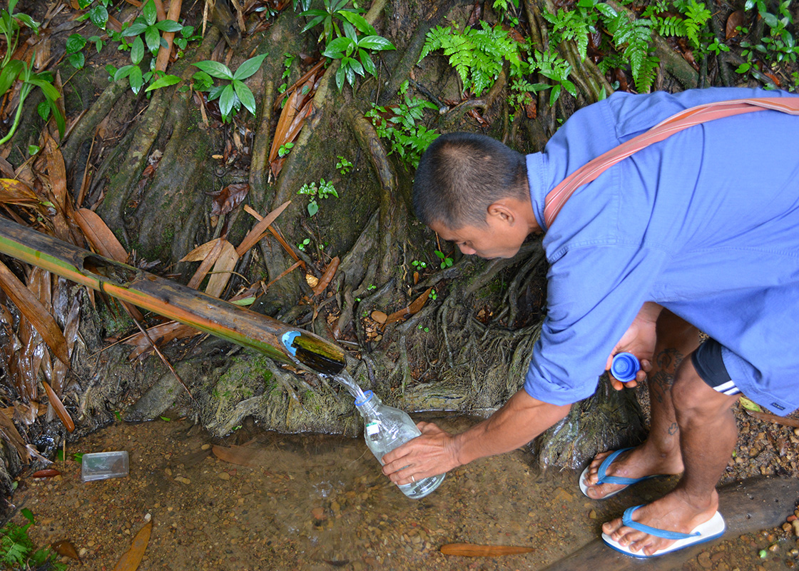 Taedee collecting water samples from the communities, his routine every morning