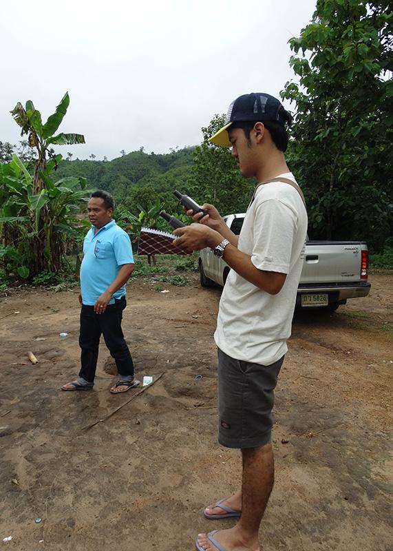 Sutthisak marking key landmarks on the GPS while visiting the communities