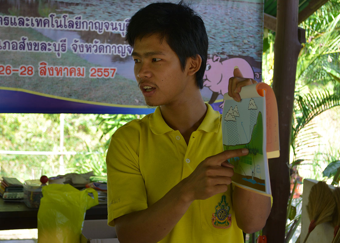 A participant presenting his water-cycle drawing, in Karen.