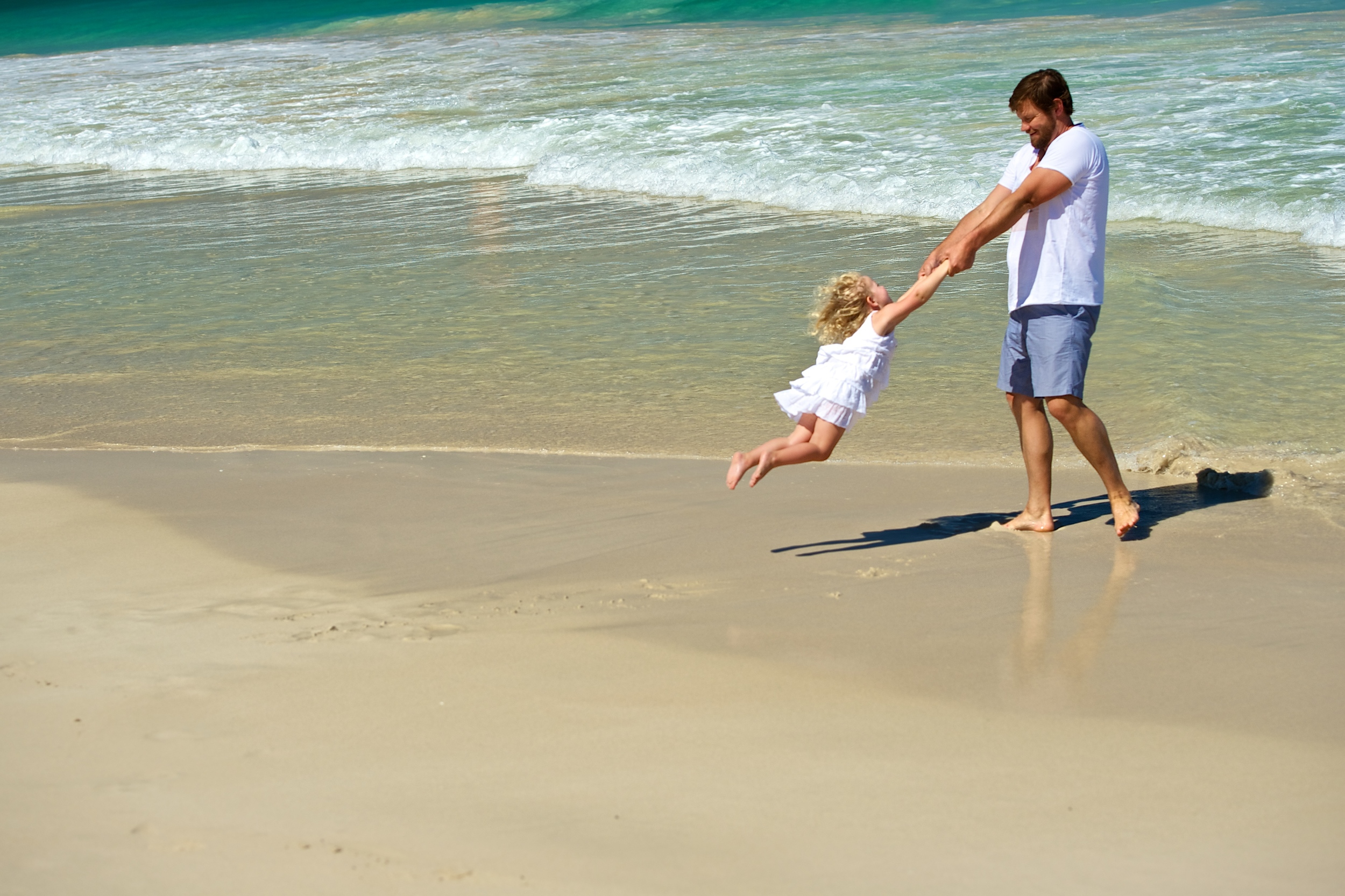 A Dad spins his daughter at the beach in this amazing family photo