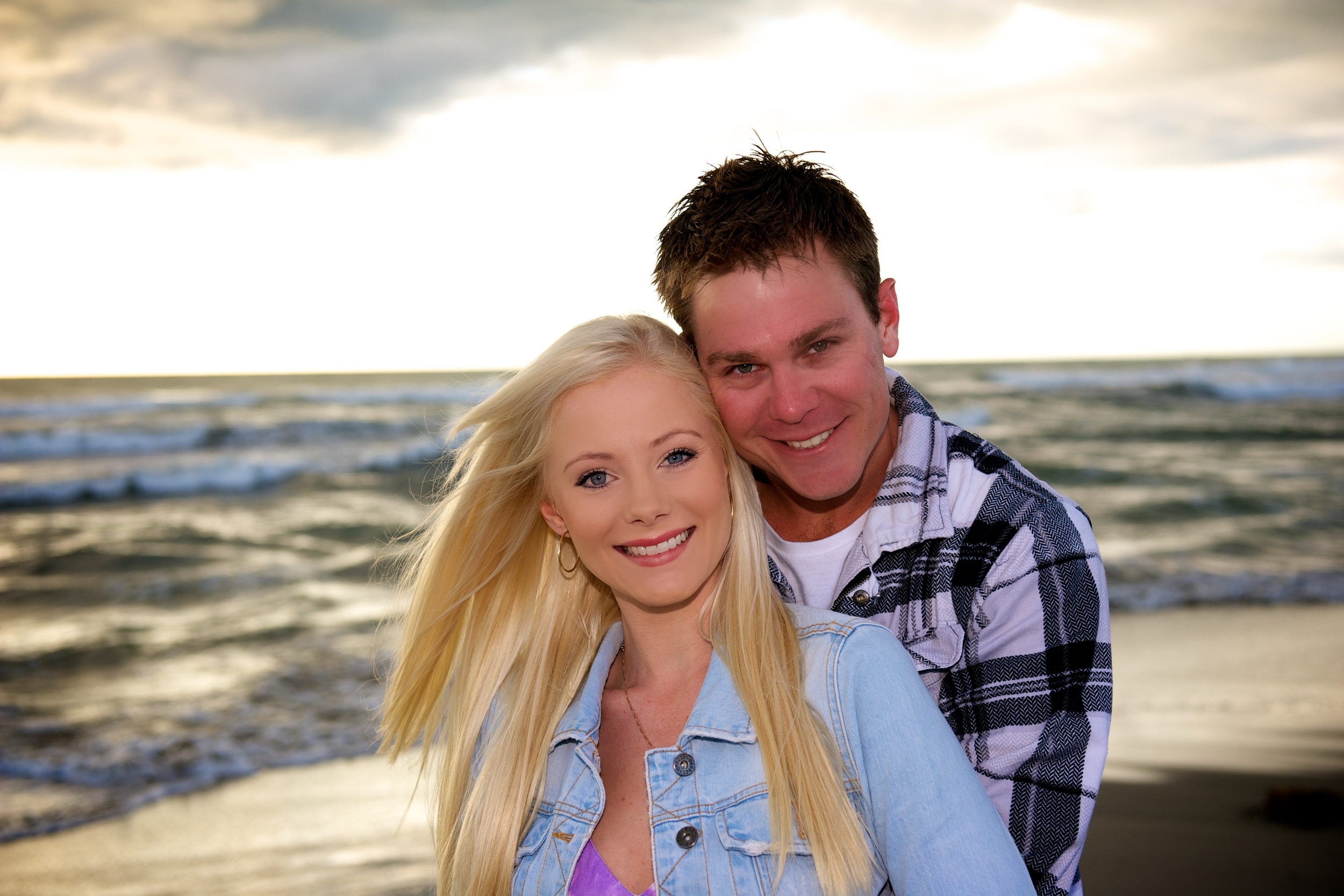An amazing image at sunset on the beach of a loving engaged couple