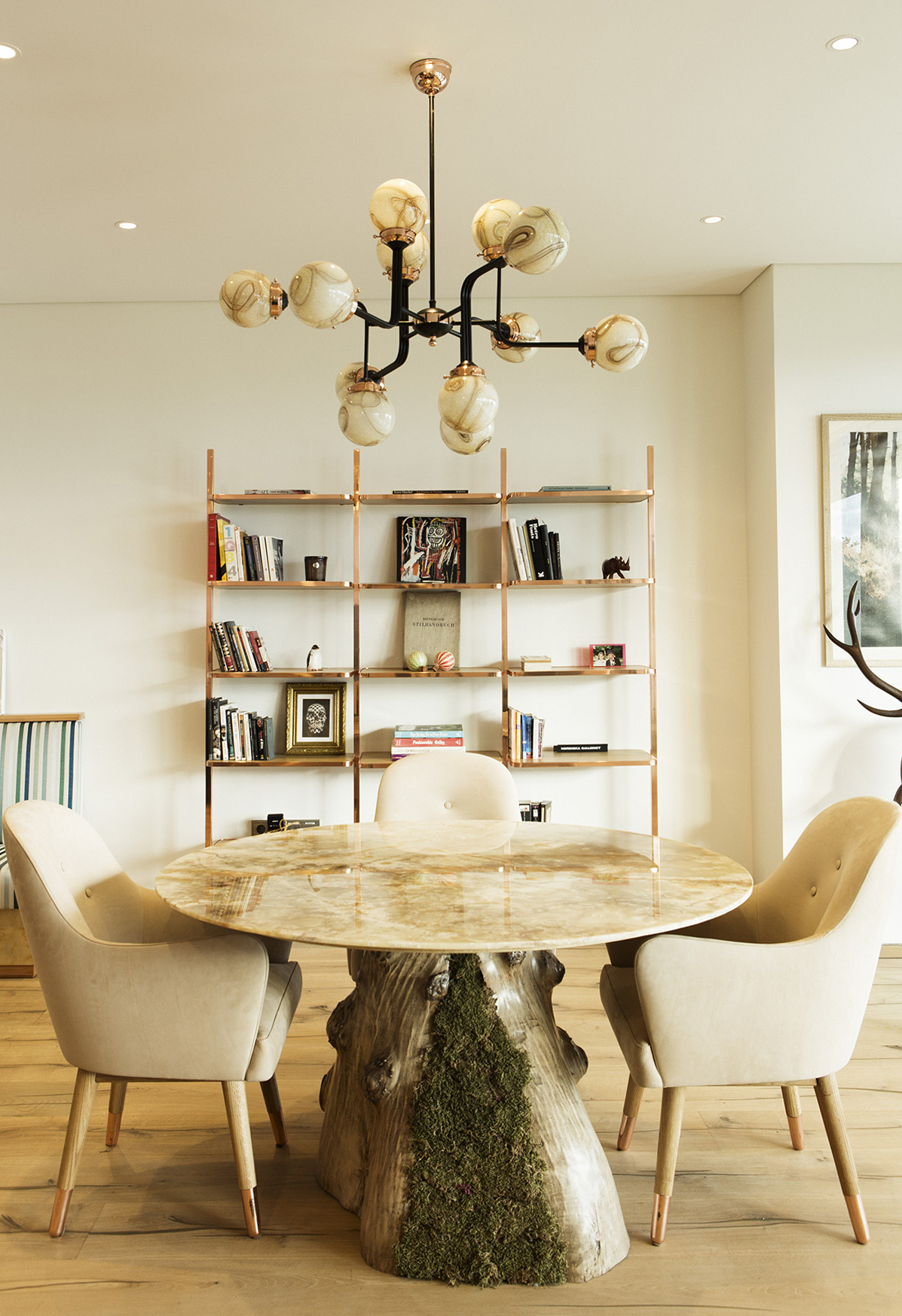 Dining Area. Custom designed onyx marble table with split root and moss, dandy chairs, cyclopedia bookshelf.