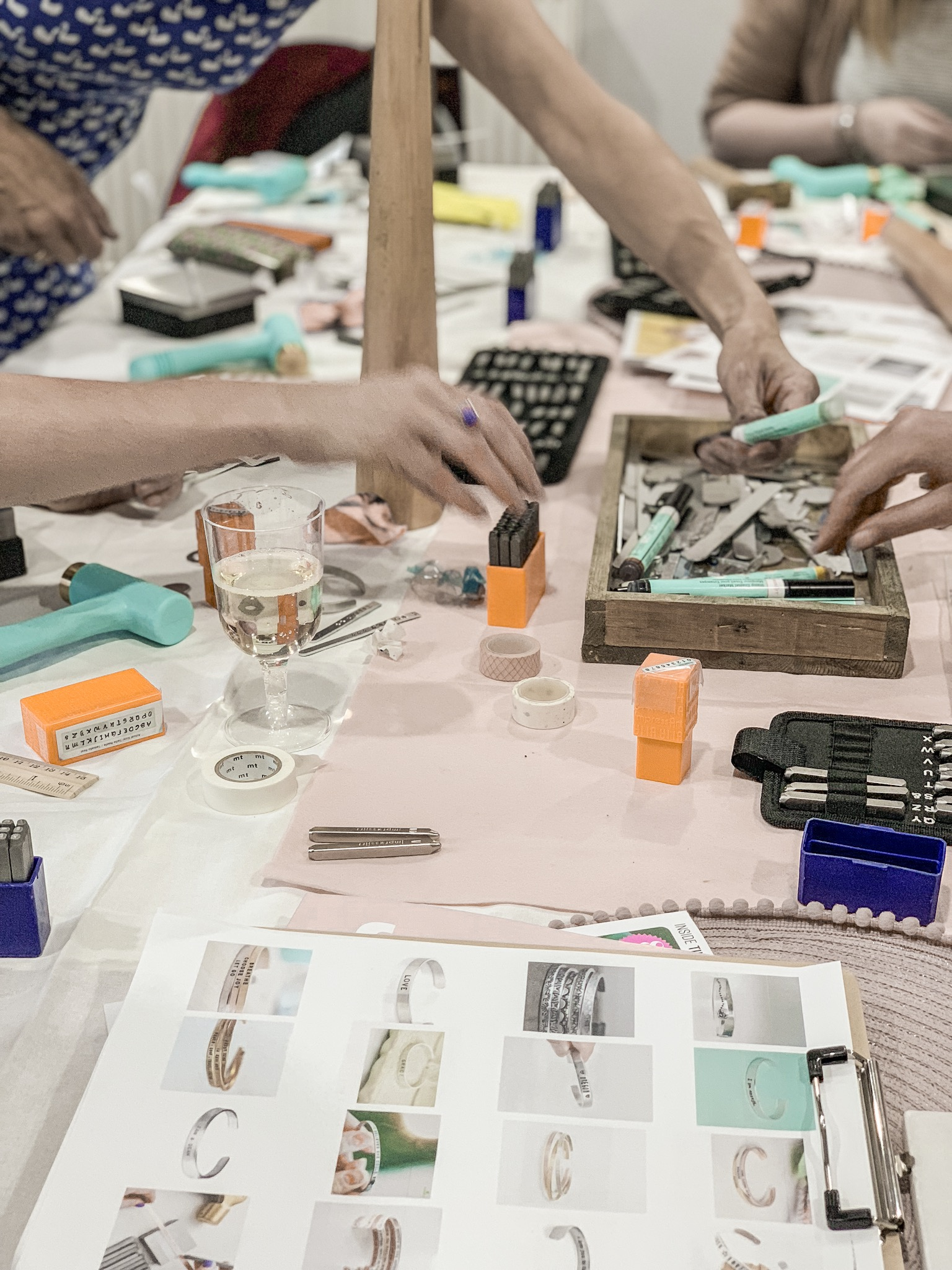 Busy hands making hand stamped jewellery at a workshop in Bristol