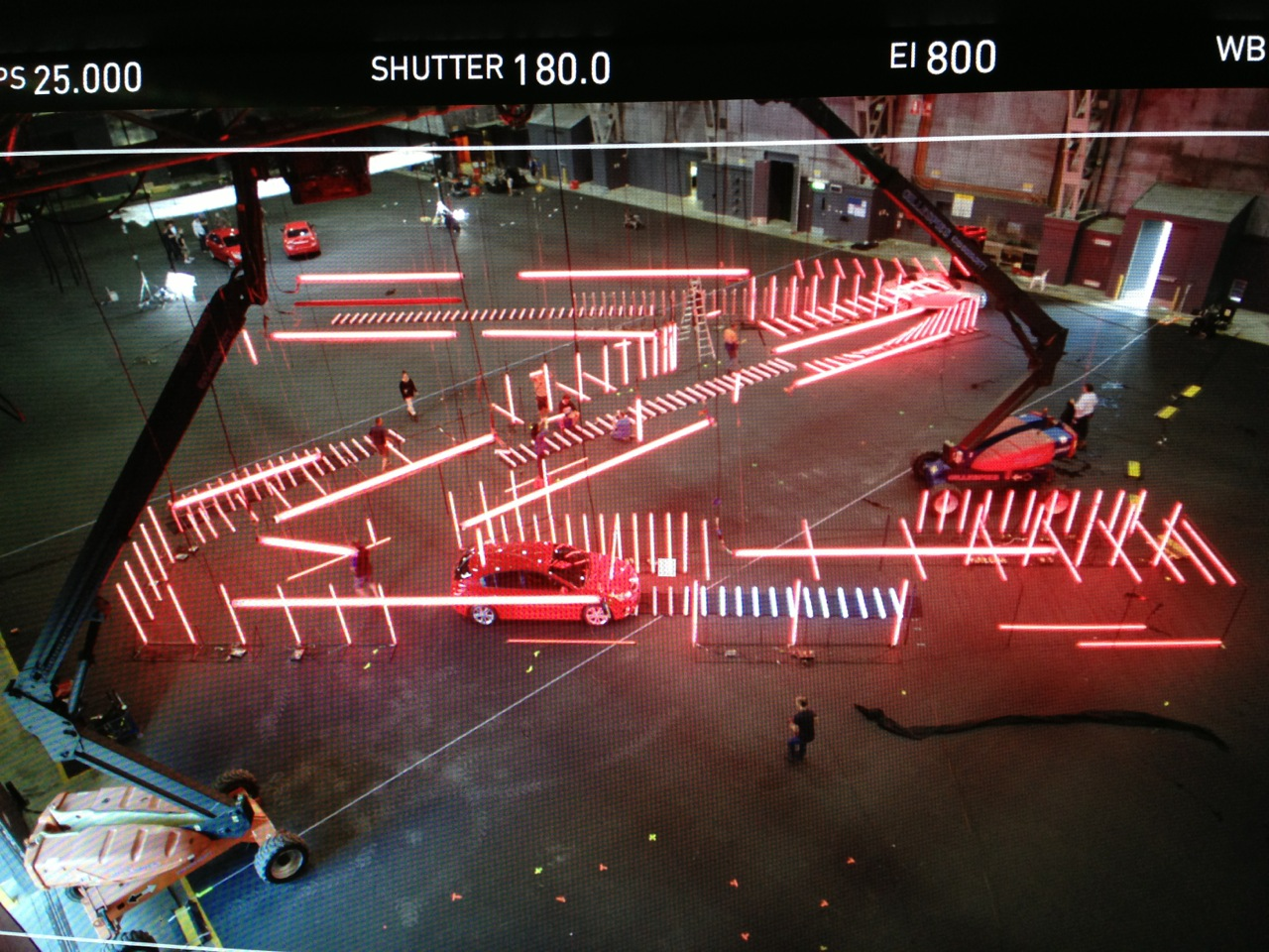 Camera tape on studio floor indicates set out positions of lighting hanging from ceiling grid in extreme foreground