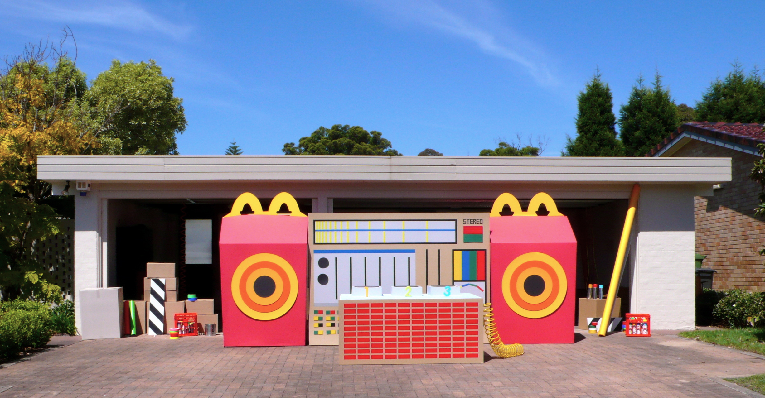 giant oversized stereo constructed out of cardboard & coloured gaffa tape with giant happy meal as speaker
