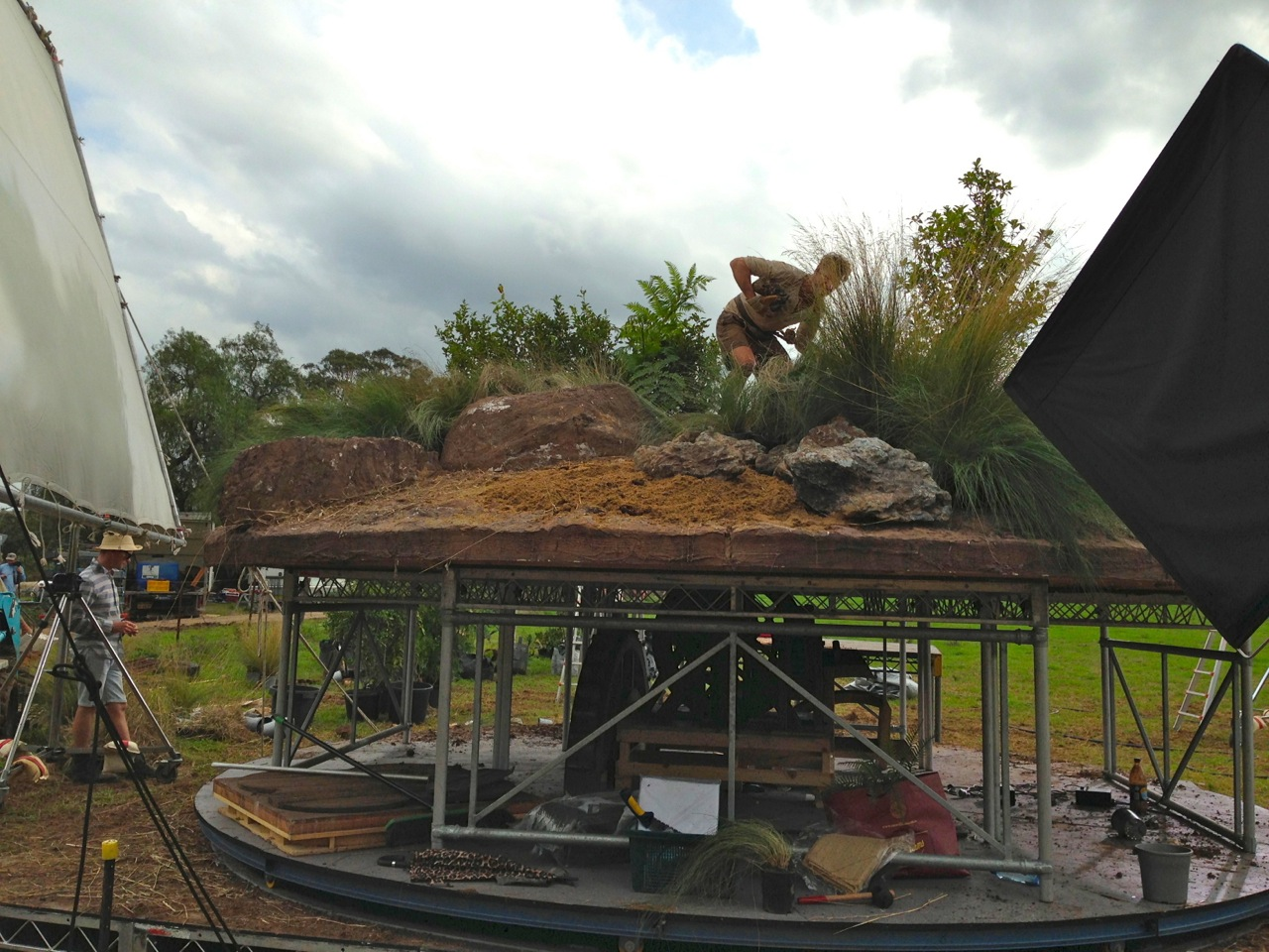 Full scale section of top of boulder built on elevated turntable to simulate turning planet shoot empty then progressively dressed with plants and small boulders