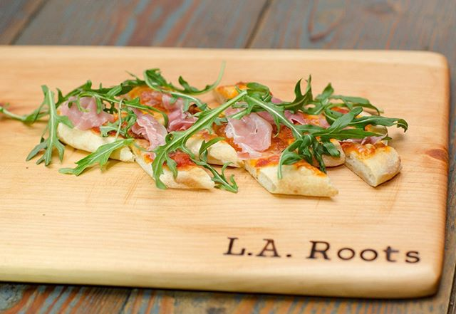 With kids going back to school soon, we can bet that pizza will be on the dinner menu here and there. How about kicking it up a notch with our Prosciutto & Arrabiata Flatbread w- Shaved Reggiano Parmesan, Wilted Arugula, Prosciutto, Spicy Arrabiata Tomato Sauce, & Fig Balsamic Reduction. #larootscatering